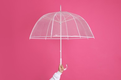 Woman with open transparent umbrella on pink background, closeup