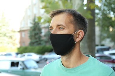 Man wearing handmade cloth mask outdoors. Personal protective equipment during COVID-19 pandemic