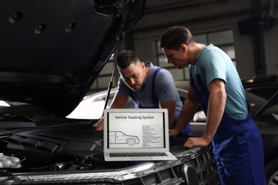 Laptop with vehicle tracking system and blurred mechanics on background. Auto diagnostic