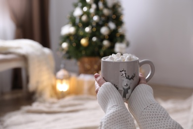 Woman with delicious hot drink at home, closeup. Space for text