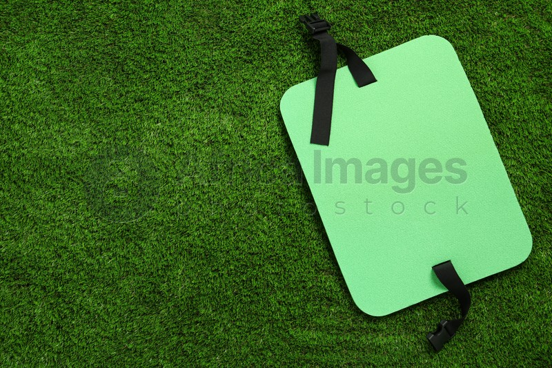 Bright foam tourist seat mat on green grass, top view. Space for text