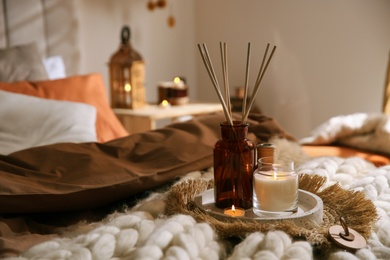 Air reed freshener and burning candles on bed indoors, space for text. Interior elements