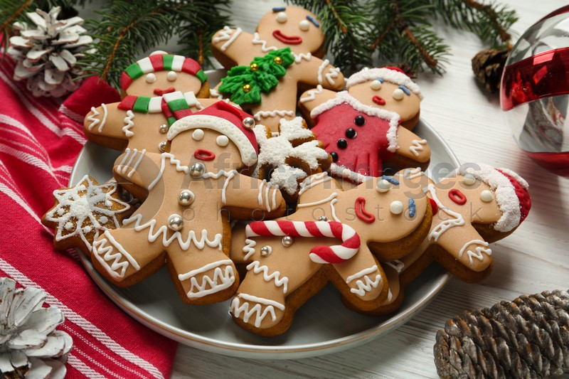 Delicious Christmas cookies, pine cones and fir branches on white wooden table
