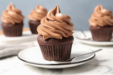 Delicious fresh chocolate cupcake on white marble table, closeup