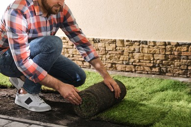 Young man laying grass sod on ground at backyard, closeup. Space for text