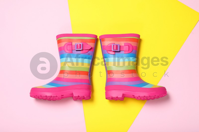 Pair of striped rubber boots on color background, top view