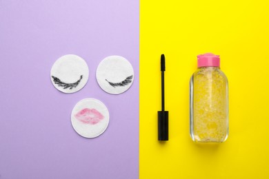 Dirty cotton pads, mascara and micellar cleansing water on color background, flat lay