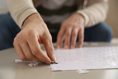 Man playing with puzzles at table, closeup