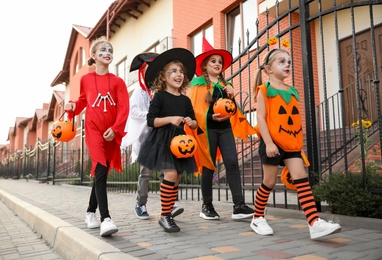 Cute little kids wearing Halloween costumes going trick-or-treating outdoors