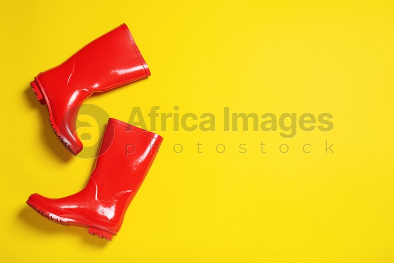 Pair of red rubber boots on yellow background, top view. Space for text