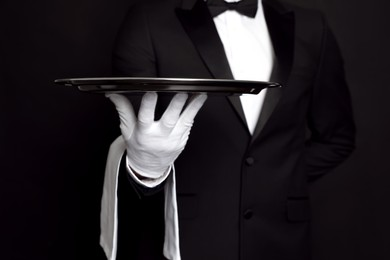 Butler with tray on black background, closeup