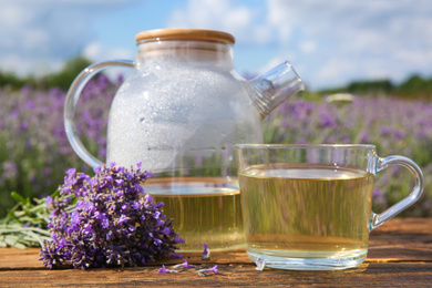 Tasty herbal tea and fresh lavender flowers on wooden table in field, closeup