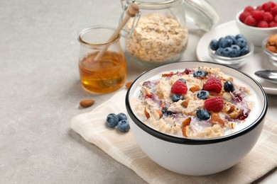 Tasty oatmeal porridge with toppings served on grey table. Space for text