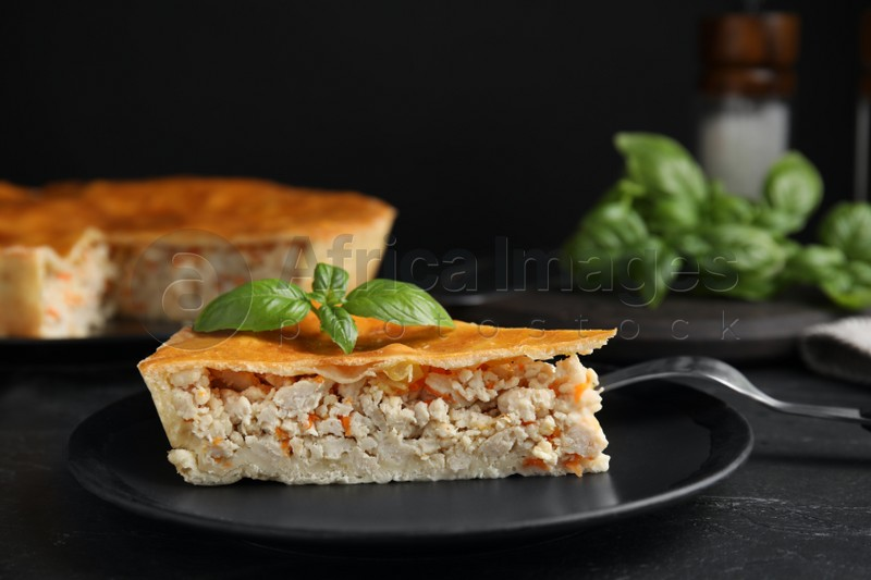 Piece of delicious pie with meat and basil on black table