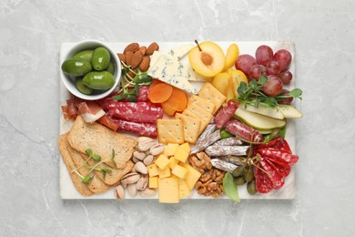 Different tasty appetizers on light marble table, top view