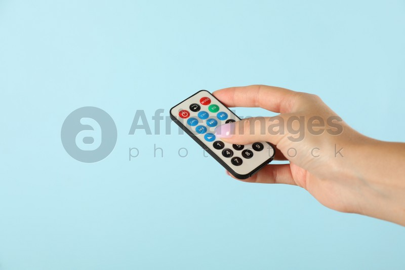 Woman holding remote control on light blue background, closeup. Space for text