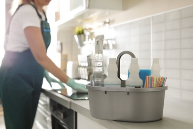 Basin with cleaning supplies on table and professional janitor in kitchen