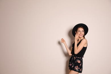Young woman wearing floral print shorts and stylish hat on beige background. Space for text