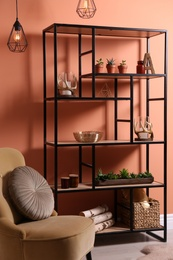 Armchair near shelving with different decor, houseplants and firewood in room. Interior design