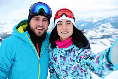 Young couple taking selfie at mountain resort. Winter vacation