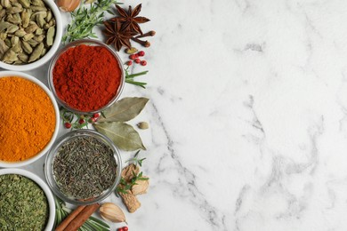 Flat lay composition with different natural spices and herbs on white marble table, space for text