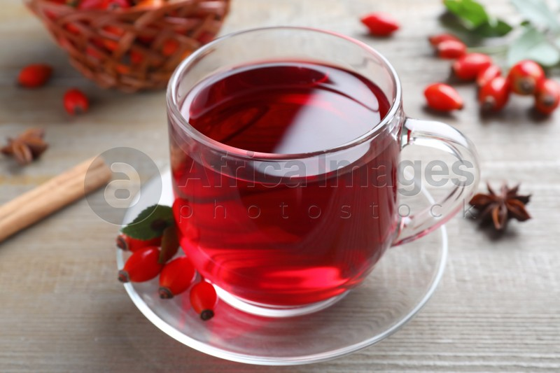 Aromatic rose hip tea and fresh berries on wooden table, closeup