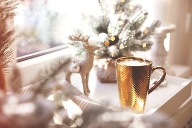 Golden cup of cocoa and Christmas decor on window sill indoors