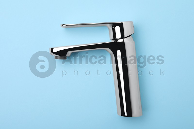 Single handle water tap on light blue background, top view