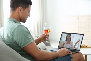 Friends drinking wine while communicating through online video conference at home. Social distancing during coronavirus pandemic