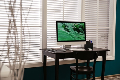 Comfortable workplace near window with white horizontal blinds in room