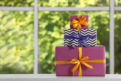 Stack of beautifully wrapped gift boxes on white table  near window. Space for text