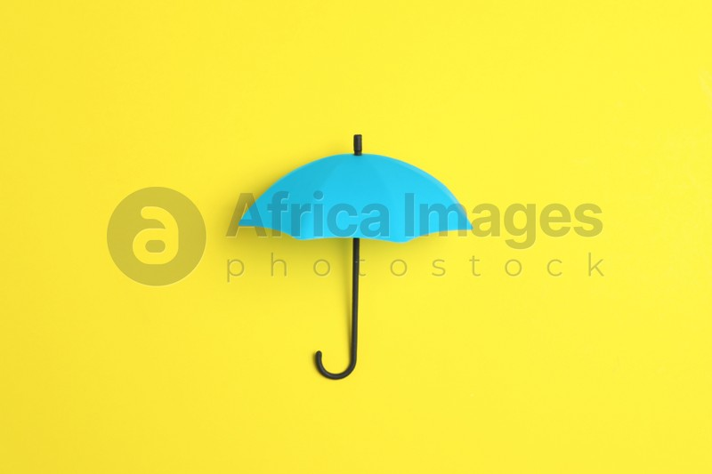Bright toy umbrella on yellow background, top view