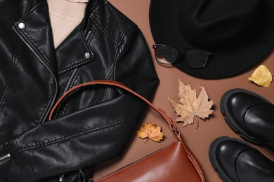 Flat lay composition with stylish hat and autumn clothes on brown background