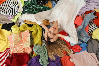 Young woman lying on pile of different clothes, top view. Fast fashion concept