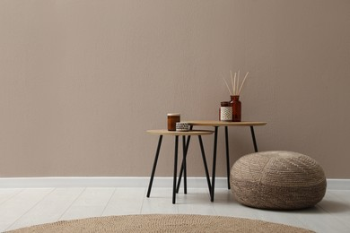 Knitted pouf and decor elements near beige wall indoors. Space for text