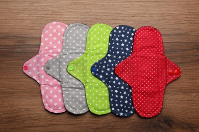 Many reusable cloth menstrual pads on wooden table, flat lay