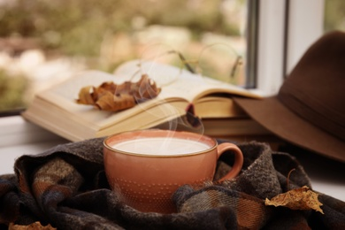 Cup of hot coffee and warm scarf on window sill indoors