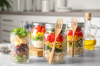 Glass jars with healthy meal on light grey marble table