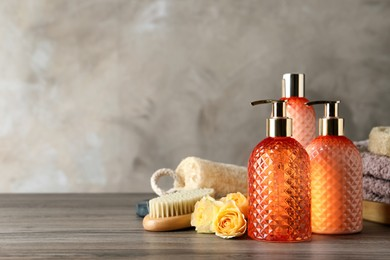 Stylish dispensers with liquid soap and other bathroom amenities on wooden table, space for text