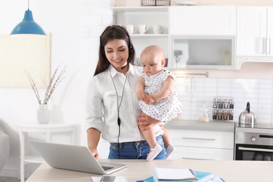 Young mother with her cute baby girl working at home