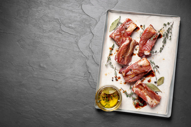 Raw marinated ribs on black table, top view. Space for text