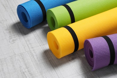 Bright rolled camping mats on white wooden background, closeup