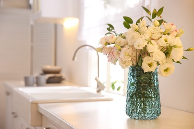 Bouquet of beautiful flowers on countertop in kitchen, space for text. Interior design