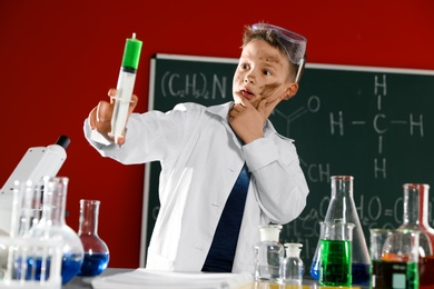 Child doing chemical research in laboratory. Dangerous experiment