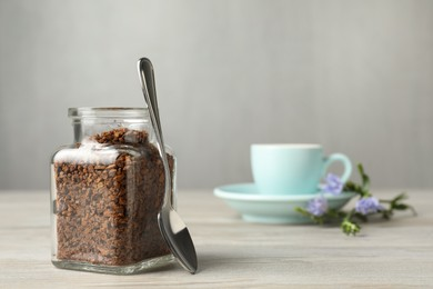 Jar of chicory granules and spoon on white wooden table, space for text