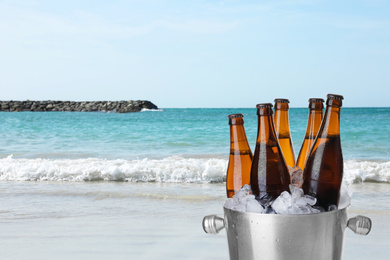 Bottles of beer with ice cubes in metal bucket against ocean and sandy beach. Space for text