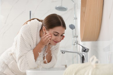 Young woman washing her face with water in bathroom