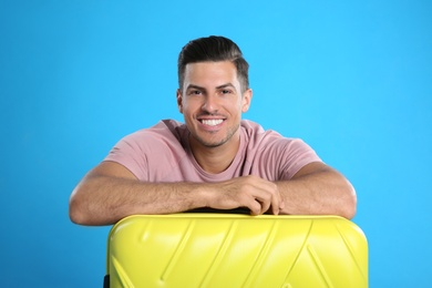 Happy man with suitcase for summer trip on blue background. Vacation travel