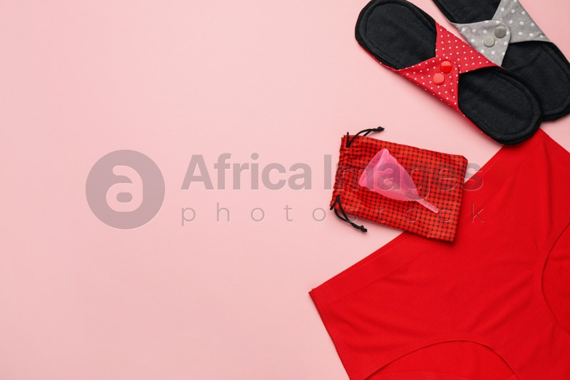 Women's underwear, reusable cloth pads and menstrual cup on pink background, flat lay. Space for text
