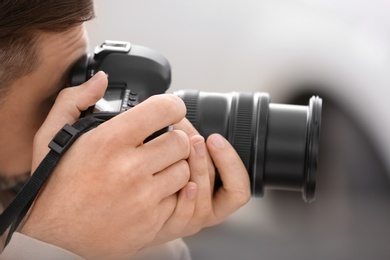 Male photographer with professional camera on blurred background, closeup